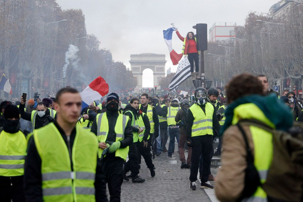 Demonstrators march on the famed Champs-Elysees avenue in Paris, France, as they protest higher fuel prices on Nov. 24, 2018.