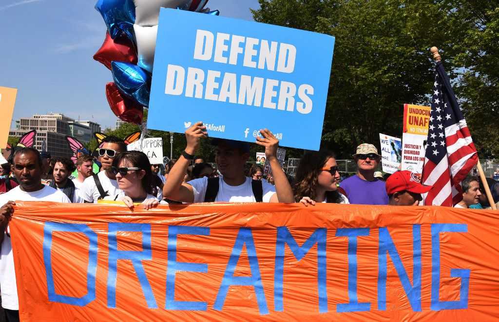 Protesters hold up  signs during a rally supporting Deferred Action for Childhood Arrivals, or DACA, outside the White House on Tuesday.