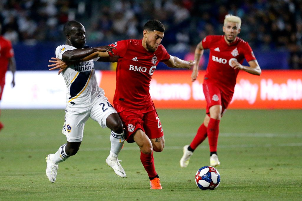 LA Galaxy's Emmanuel Boateng, left, defends against Toronto FC midfielder Jonathan Osorio, center, during the first half of an MLS soccer match in Carson, Calif., Thursday, July 4, 2019. (AP Photo/Ringo H.W. Chiu)