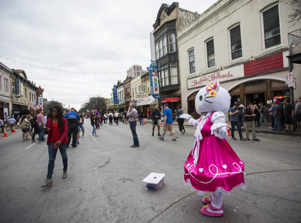 A street performer dressed as Hello Kitty blows kisses to a fairly empty Sixth Street during the 2015 SXSW interactive and film festival on Sunday, March 15 in downtown Austin.