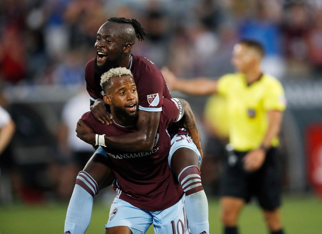 Colorado Rapids forward Kei Kamara, top, jumps on midfielder Kellyn Acosta after he scored a goal against the San Jose Earthquakes in the first half of an MLS soccer match Saturday, Aug. 10, 2019, in Commerce City, Colo. (AP Photo/David Zalubowski)