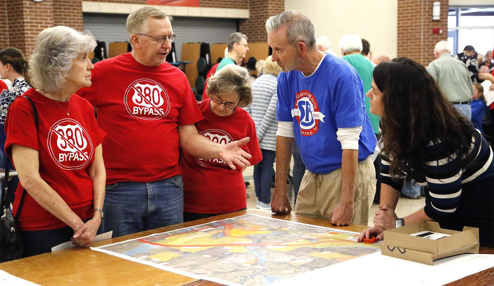 From left: Cindy Vogel of Walnut Grove, Gary Pierce of Walnut Grove and wife Melinda, Ron Cagle of Stonebridge Ranch and project consultant Chelsey Smith talked over questions as residents met to look at maps of the latest iteration of the proposed bypass for Highway 380 at Rogers Middle School in Prosper on Thursday.