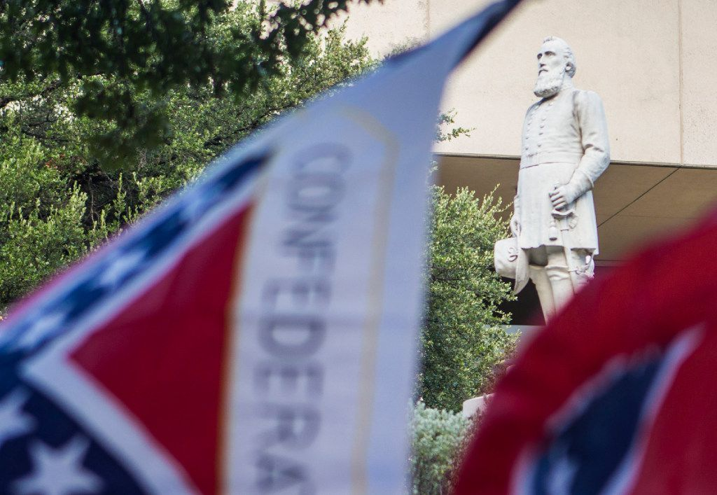 Confederate flags are flown by counter-protesters during a rally for removal of Dallas' Confederate monuments and public buildings named for Confederate heroes at Pioneer Park Cemetery in Dallas on Thursday, August 10, 2017. (Ryan Michalesko/The Dallas Morning News)
