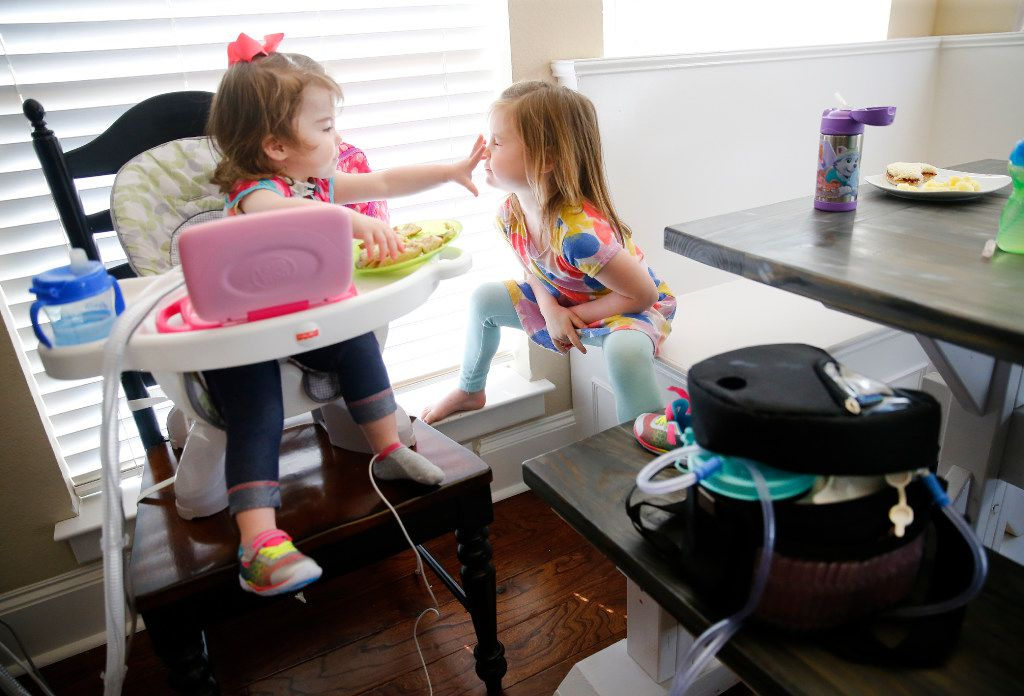 Christina Gregory (left), who suffers from CCHS (Congenital Central Hypoventilation Syndrome), a genetic disorder that affects her breathing, plays with her older sister Grace during her lunch time, Tuesday, January 31, 2017. While she eats, there is a ventilator unit that hooks up to a trachea tube in her neck to assist in breathing when needed.  The Gregory's have two pediatric nurses that keep a watchful eye on Christina at their Southlake,Texas home. The family is affected by Texas' change to their Medicare healthcare coverage, switching to a MCO plan from an HMO plan, limiting their care to within the region -a cumbersome issue for families dealing with 24/7 care. (Tom Fox/The Dallas Morning News)