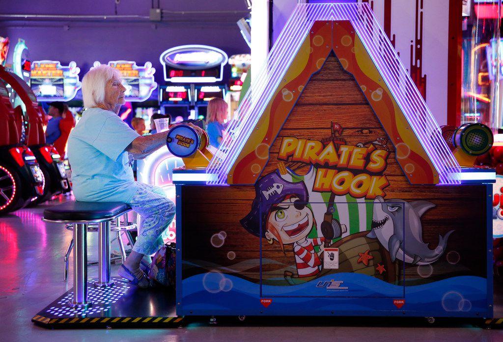 Roena White plays an arcade game at NickelRama in Garland.