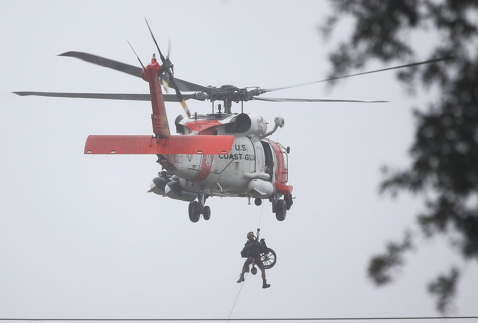 A Coast Guard helicopter hoists a wheel chair on board after lifting a person to safety  from the area that was inundated with flooding from Hurricane Harvey on August 28, 2017 in Houston, Texas.