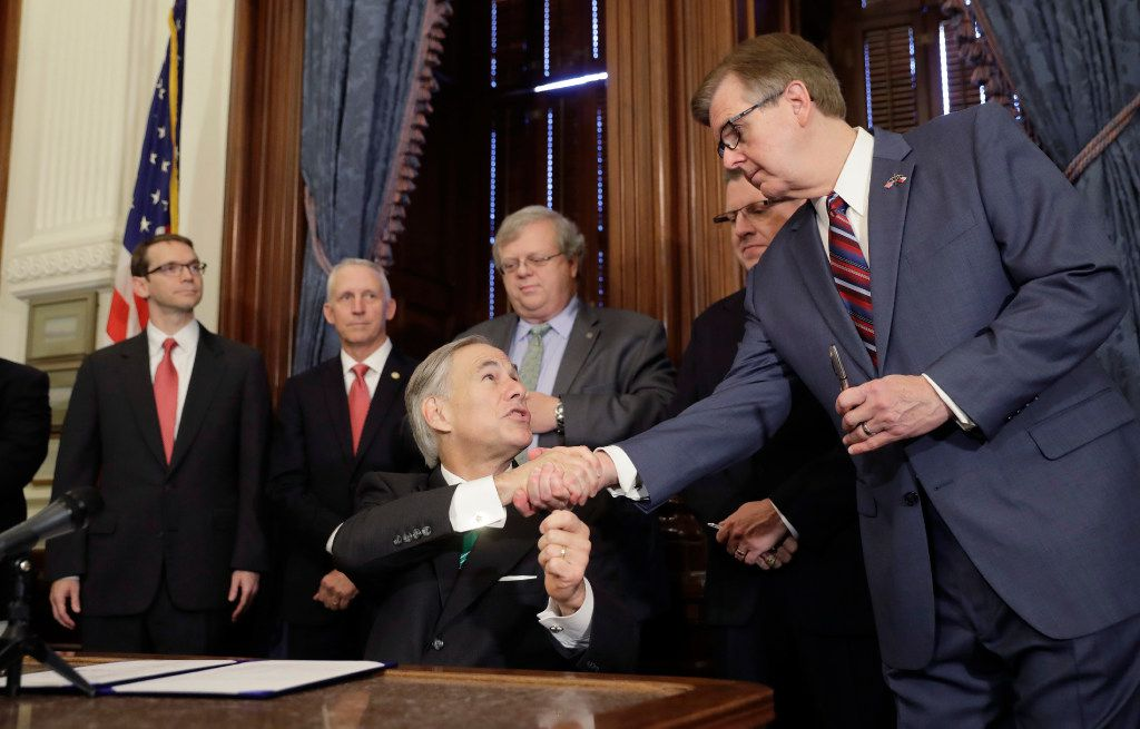 Gov. Greg Abbott, center, shakes hands with Lt. Gov. Dan Patrick after he signed SB7, a bill to address inappropriate teacher-student relationships.