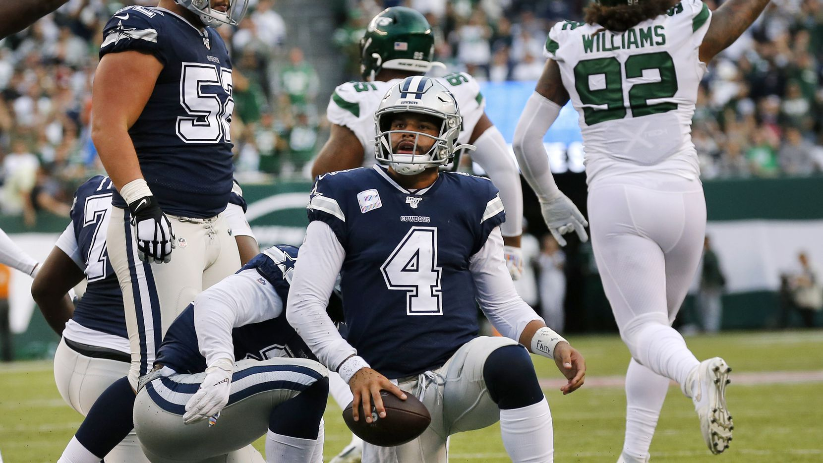 Dallas Cowboys quarterback Dak Prescott (4) gets back to his feet after being stopped short on 4th down and 2 against the New York Jets in the second quarter during at MetLife Stadium in East Rutherford, New Jersey, Sunday, October 13, 2019. Rookie defensive tackle Quinnen Williams, the No. 3 overall pick, (right) celebrates after chasing down Prescott from behind.