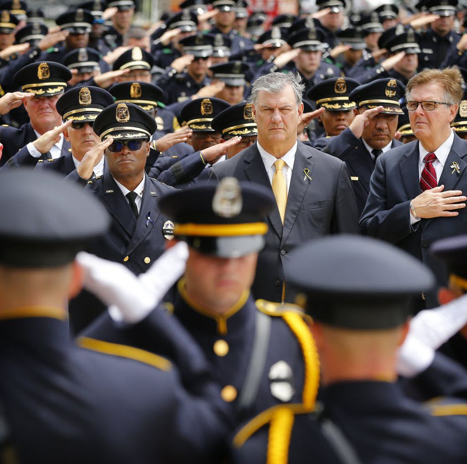 (from left) Dallas police Chief David Brown (facing with sunglasses), Dallas Mayor Mike Rawlings  and Texas Lt Gov. Dan Patrick watch as the Dallas Police Honor Guard salutes carries the flag-draped casket of Dallas police officer Michael Krol outside of Prestonwood Baptist Church in Plano, Texas, Friday, July 15, 2016.  (Tom Fox/The Dallas Morning News, pool photo)