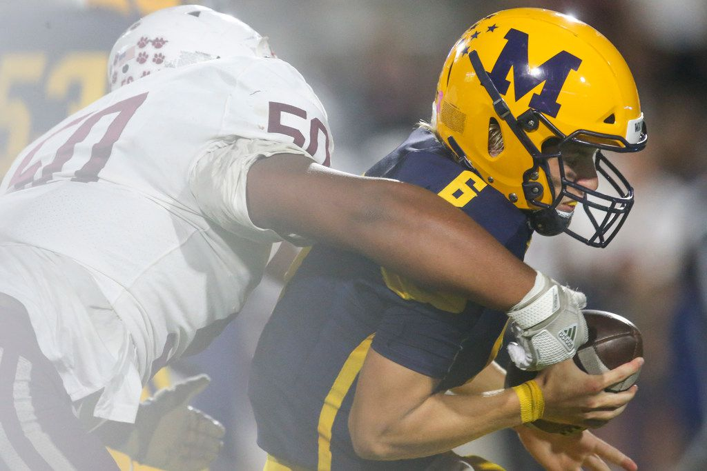 McKinney quarterback gets sacked by Plano defensive lineman Devid Smith (50) during the second half of a high school football game between McKinney and Plano high schools on Thursday, October 10, 2019 at McKinney ISD Stadium in McKinney, Texas. (Shaban Athuman/Staff Photographer)