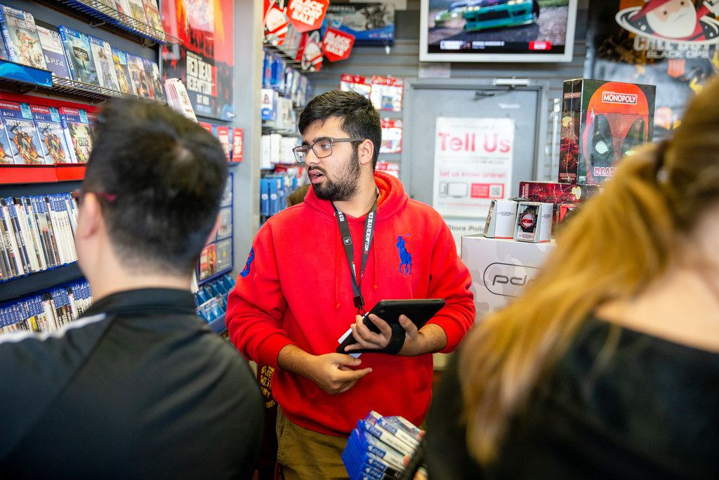 Hamza Khan suggests games for a costumer during Black Friday shopping at GameStop in Fairview on Thursday, November 22, 2018.