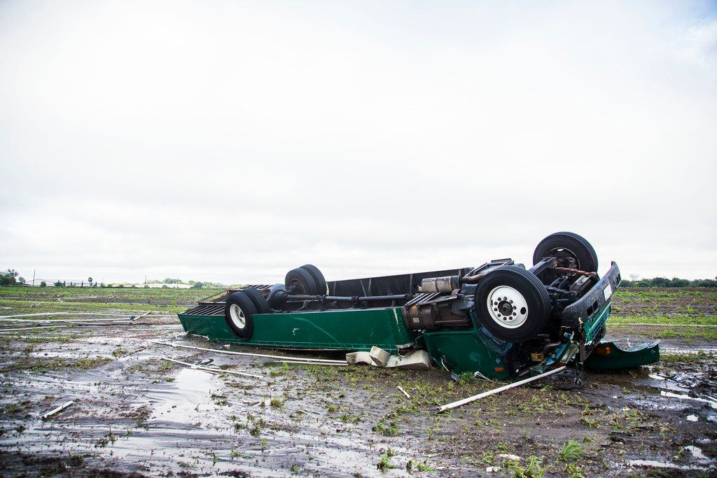 The band bus at Waxahachie High was left crumpled in a muddy field after Saturday's storm blew through.