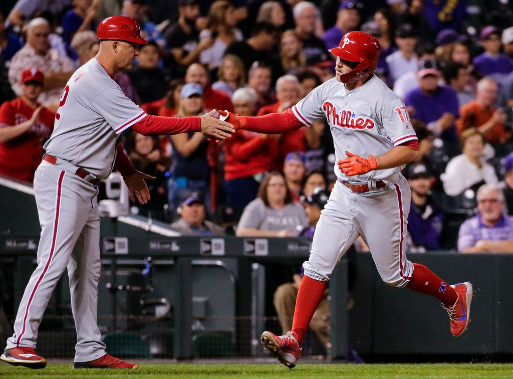 Philadelphia Phillies' Rhys Hoskins is congratulated by third base coach Dusty Wathan as he rounds the bases after hitting a solo home run against the Colorado Rockies during the seventh inning of a baseball game on Monday, Sept. 24, 2018, in Denver. (AP Photo/Jack Dempsey)