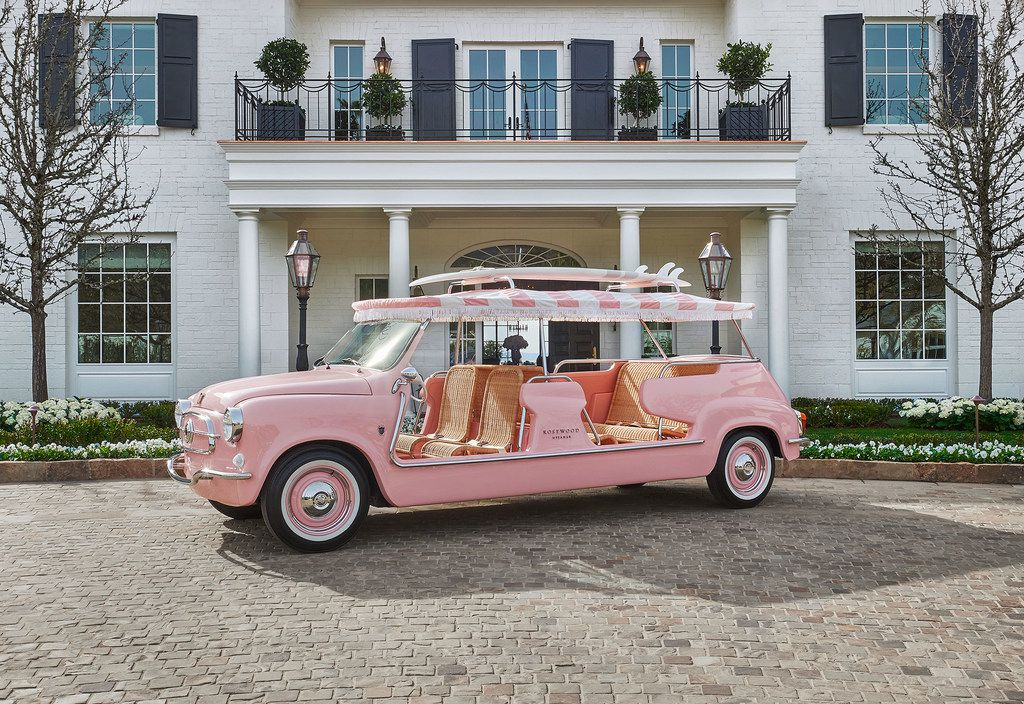 Rosewood Miramar Beach totes guests around in a pink vehicle topped with a surfboard.