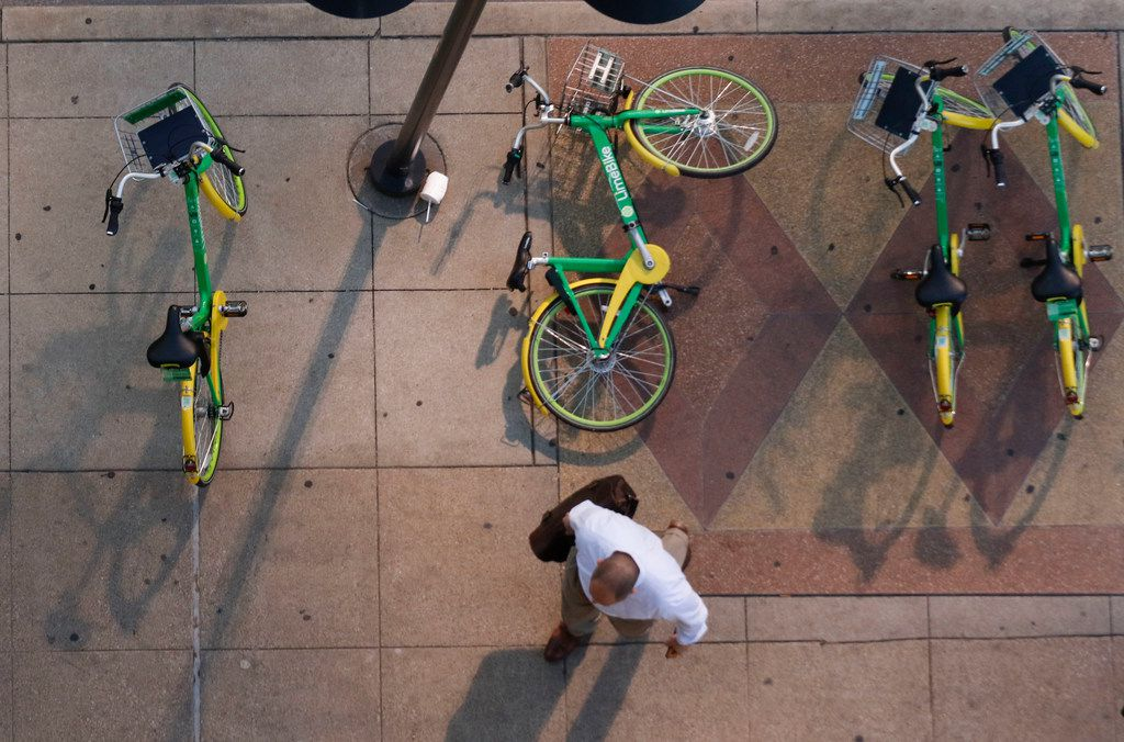 A pedestrian walks around a fallen rental bike at the corner of Harwood and Elm Streets in downtown Dallas on Tuesday, April 24, 2018. View is from a parking garage on the intersection.