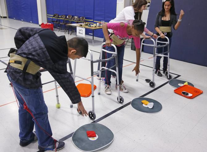 Merriman Park students Edgar Roque, Destin Smith and Leslie Casas (right) got help from volunteer Dannielle Chamness (second from right) at a station simulating mobility issues.