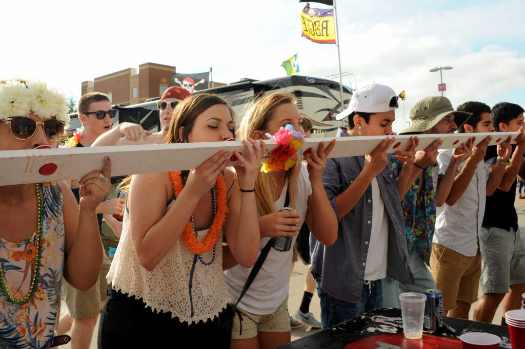 Parrotheads take a shot from a shotboard at the Jimmy Buffett tailgate party at Toyota Stadium in Frisco, TX on May 30, 2015.