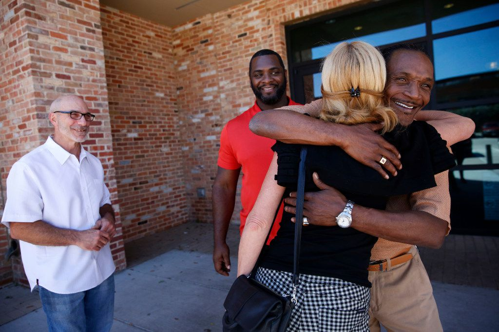 """Exoneree Johnnie Lindsey hugs Dorothy Budd, author of """"Tested: How Twelve Wrongly Imprisoned Men Held Onto Hope,"""" alongside fellow exonerees Steven Phillips (far left) and Christopher Scott before a screening of True Conviction, a documentary film by Jamie Meltzer that features the three men, at Alamo Drafthouse in Dallas. (Rose Baca/The Dallas Morning News)"""