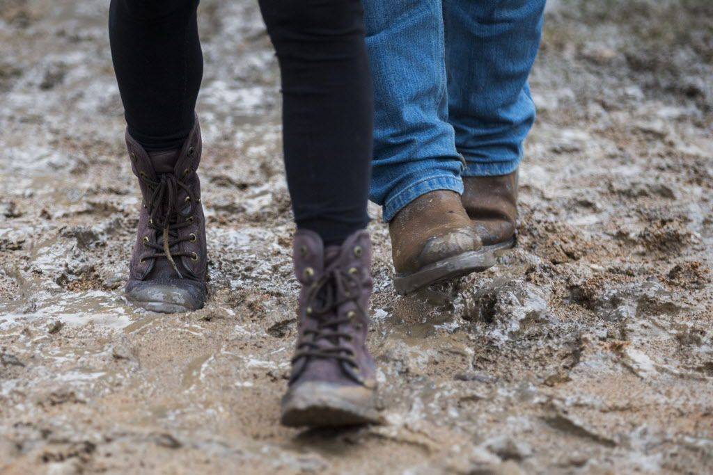 Festival attendees walk through mud and rain puddles at Hype Machine's Hype Hotel party during the SXSW music festival on Saturday, March 21, 2015 in east Austin, Texas.