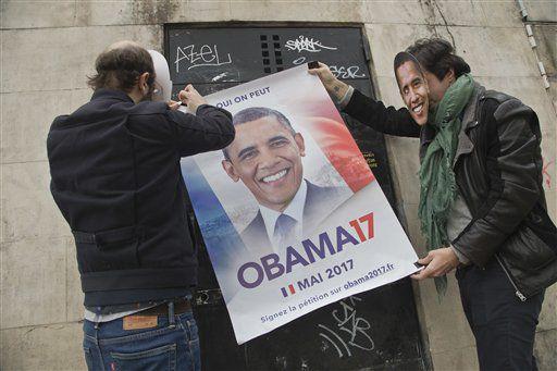 Dos dirigentes de un petitorio online conocido como Antoine y Antoine con máscaras del expresidente estadounidense Barack Obama sujetan un cartel en un muro de París. Foto de AP