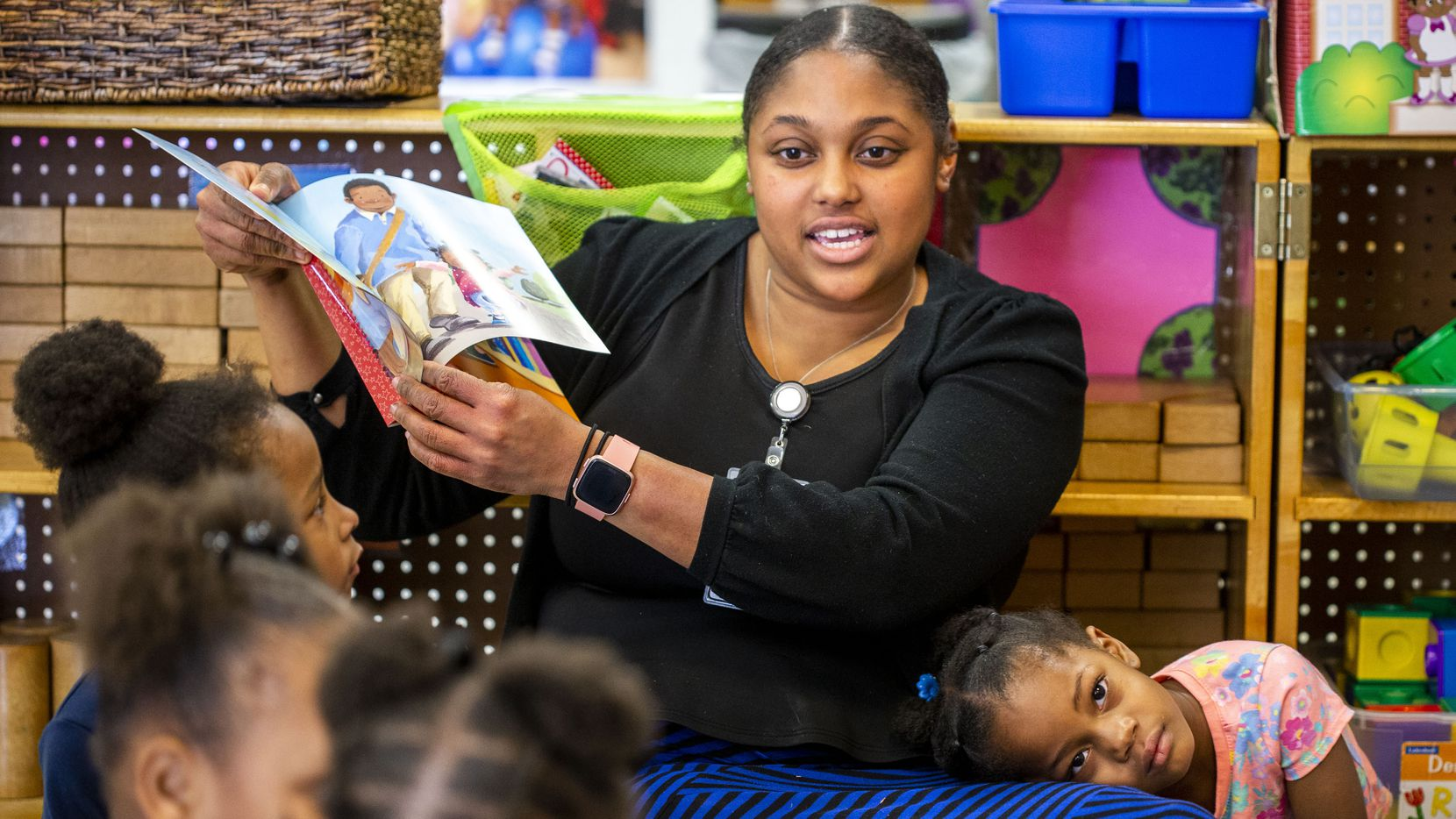Erika Littlejohn, 3, leans on Natasha Hymes as she reads a book to the class at ChildCareGroup Martin Luther King, Jr Center on Monday.