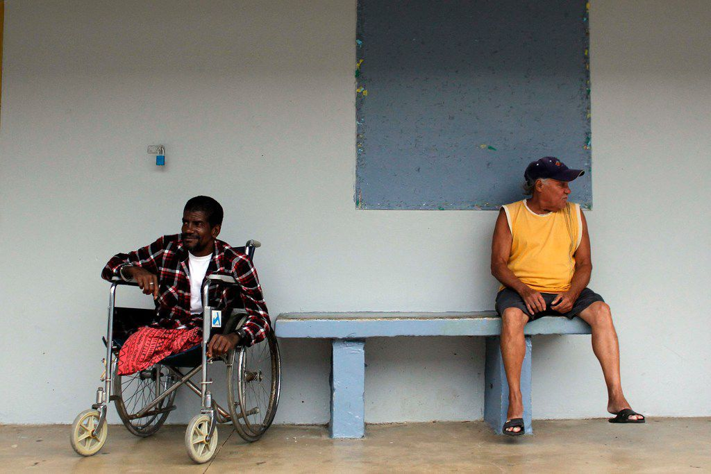 """Two men rest at a shelter as Hurricane Maria approaches Puerto Rico in Fajardo on September 19, 2017. Maria headed towards the Virgin Islands and Puerto Rico after battering the eastern Caribbean island of Dominica, with the US National Hurricane Center warning of a """"potentially catastrophic"""" impact. / AFP PHOTO / Ricardo ARDUENGORICARDO ARDUENGO/AFP/Getty Images"""