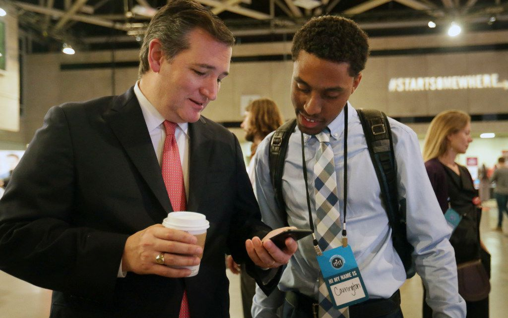 Sen. Ted Cruz, R-Texas, shares his social media post about men's rompers with job seeker Carrington Tatum at the Opportunity Fair and Forum employment event in Dallas on May 19, 2017.