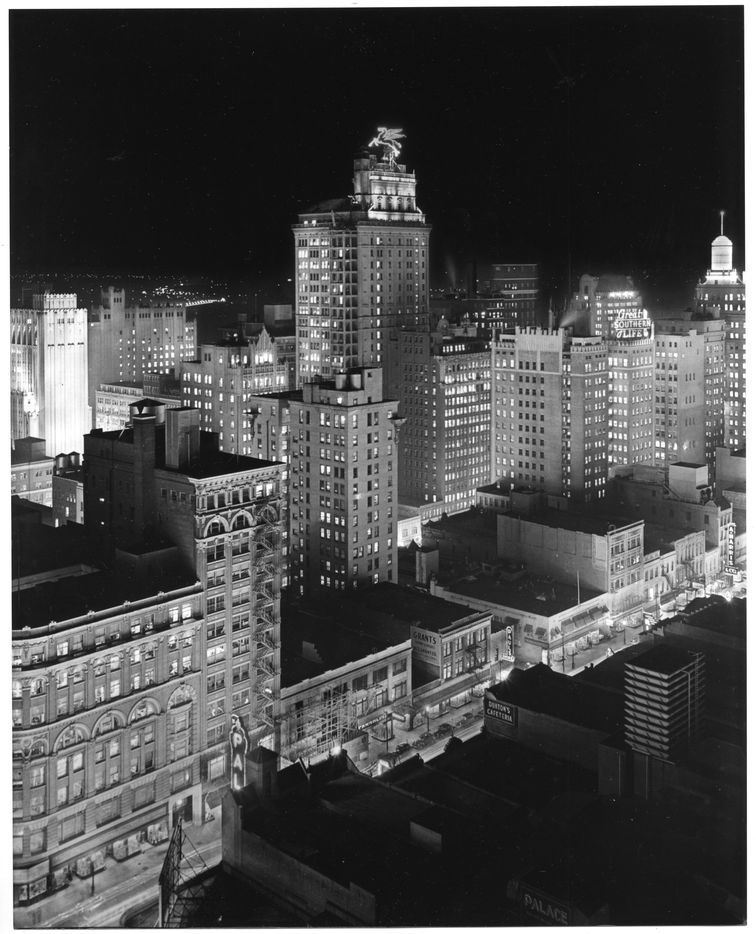 """A Dallas Historical Society photo by Lloyd Long is a dramatic night view of downtown Dallas that was taken about 1935. It shows an urban skyline dominated by the Magnolia Petroleum Building (the tallest west of the Mississippi) and its rooftop neon sign of Pegasus, """"the flying red horse."""""""