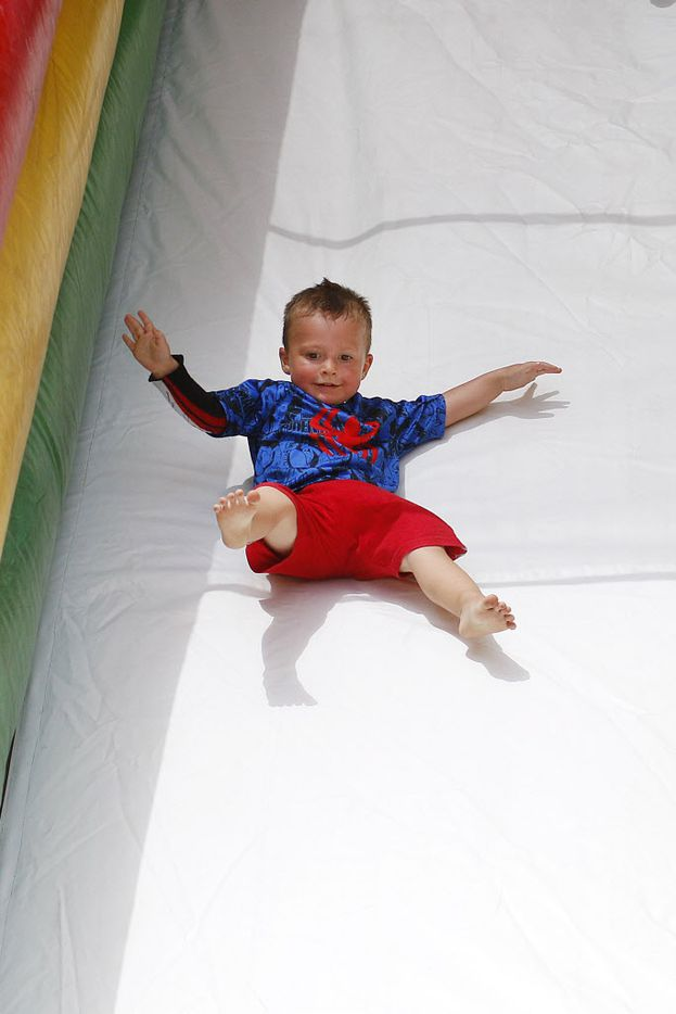 Channing Polatis, 2, rides down a inflatable slide during the Independence Fest Children's Parade and Festival in Flower Mound, Texas on Saturday, July, 4, 2015.