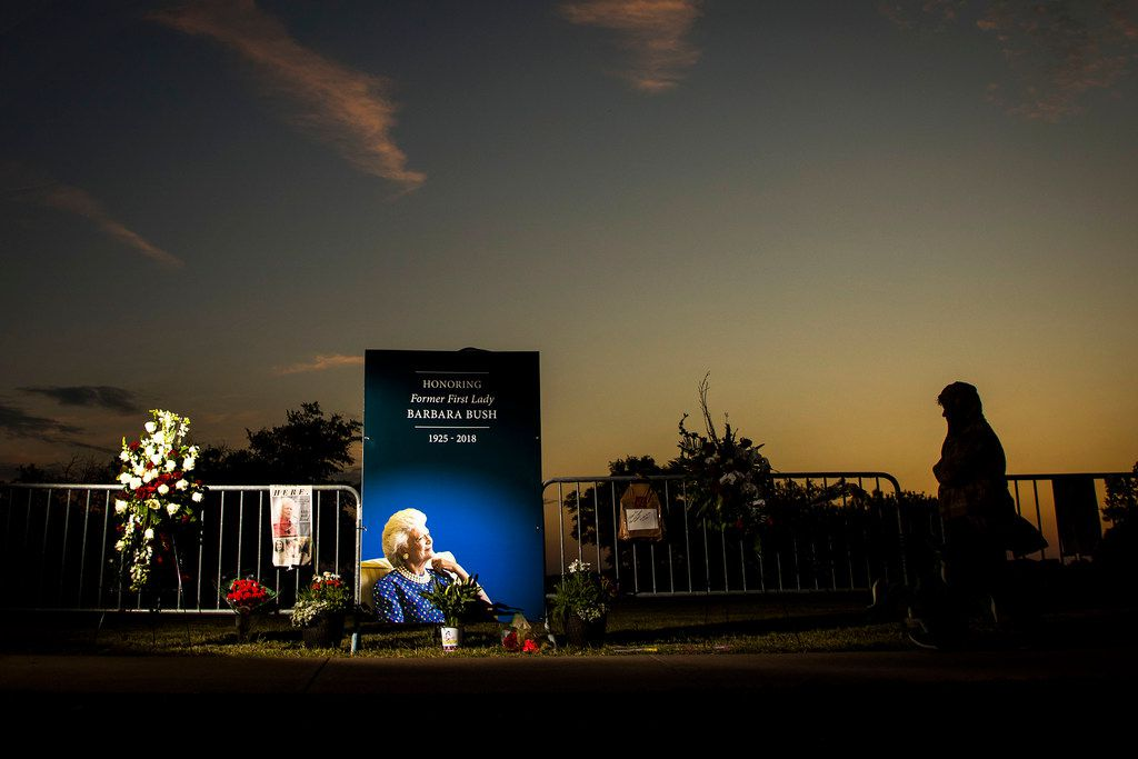 People visit a memorial to former first lady Barbara Bush as the sun sets near her husband's presidential library at Texas A&M University on Friday, April 20, 2018, in College Station.