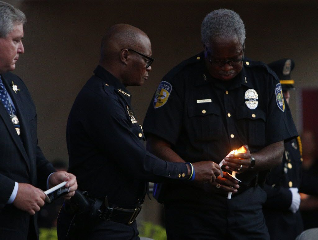 Dallas Area Rapid Transit Police Chief James Spiller (right) lights Chief David Brown's candle during Monday night's vigil at Dallas City Hall. At left is Dallas Police Association President Ron Pinkston.