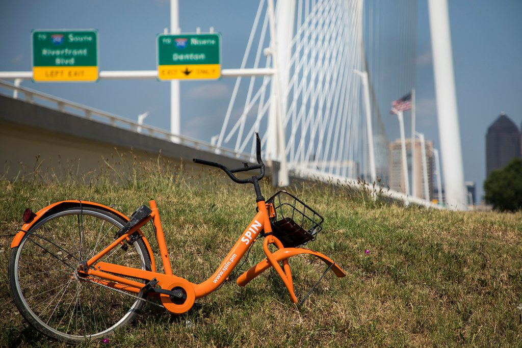 A broken Spin rental bike rests in the grass near the Margaret Hunt Hill Bridge along the Trinity Skyline Trail on Tuesday.