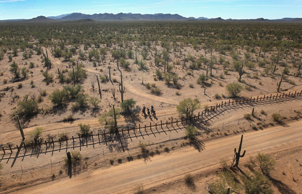 A group of young men walk along the Mexican side of the U.S.-Mexico border fence in a remote area of the Sonoran Desert on December 9, 2010 in the Tohono O'odham Reservation, Arizona.