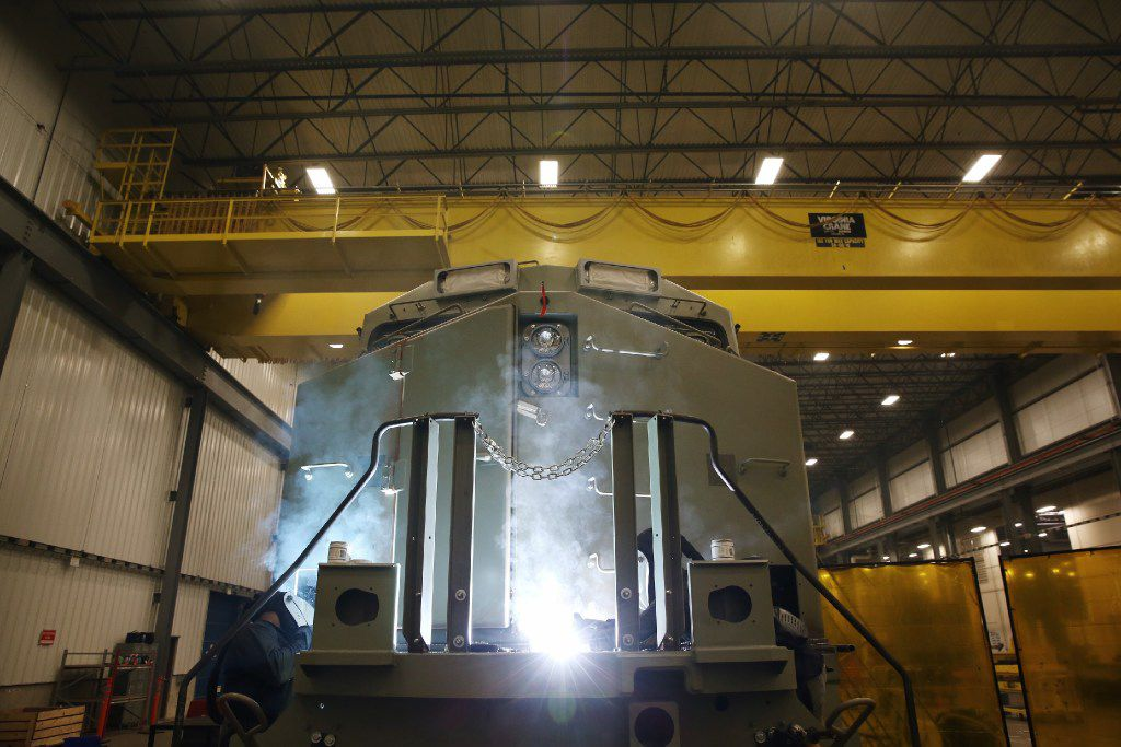 Welders work on an Evolution Series locomotive on the final assembly line at GE Manufacturing Solutions in Fort Worth. The facility completed its first locomotive in January 2013.