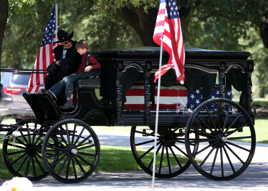 Magnus Ahrens, 8, son of fallen Dallas police Senior Cpl. Lorne Ahrens sits with the driver of a caisson bearing his father's casket during Ahrens' burial service.