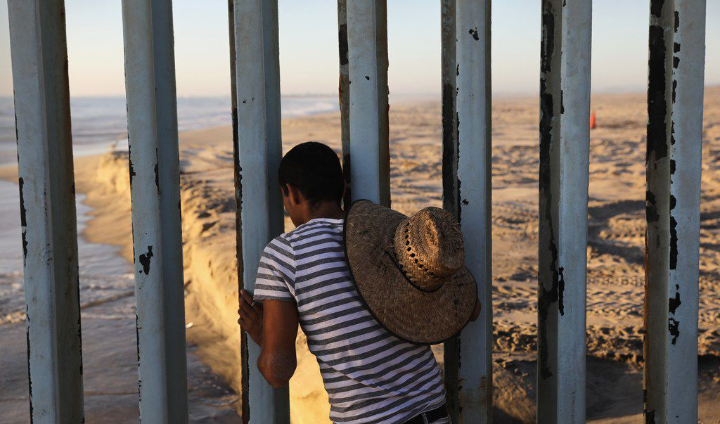 A man looks through the U.S.-Mexico border fence into the United States on September 25, 2016 in Tijuana, Mexico. Friendship Park on the border is one of the few places on the 2,000-mile border where separated families are allowed to meet.