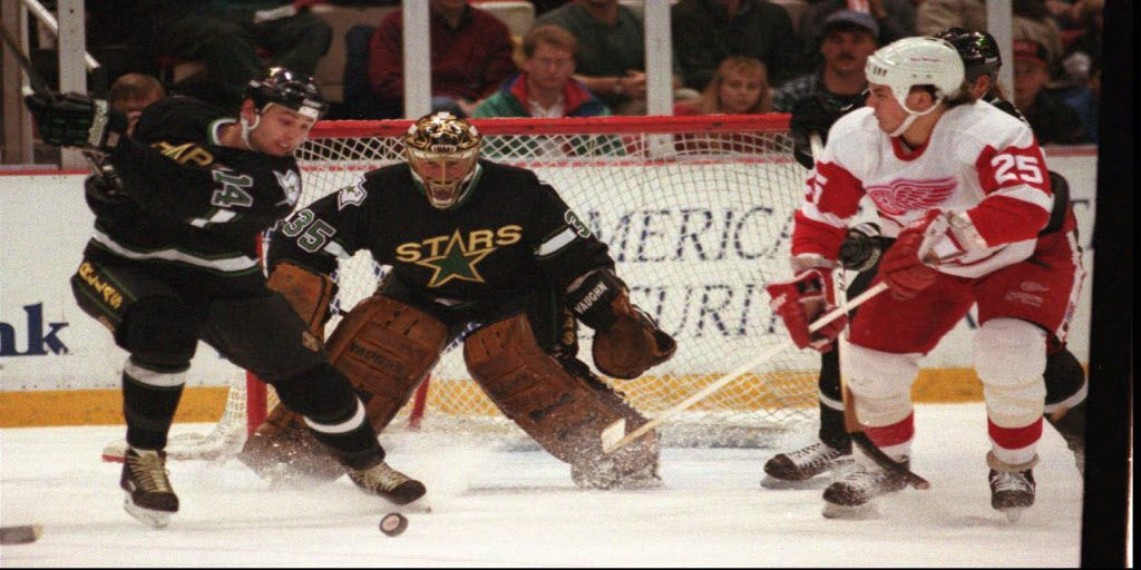 Dallas Stars goalie Andy Moog (35) watches as teammate  Paul Cavallini (14) and Detroit Red Wings Darren McCarty (25)  battle for control during the first period Saturday, Nov. 27, 1993, in Detroit