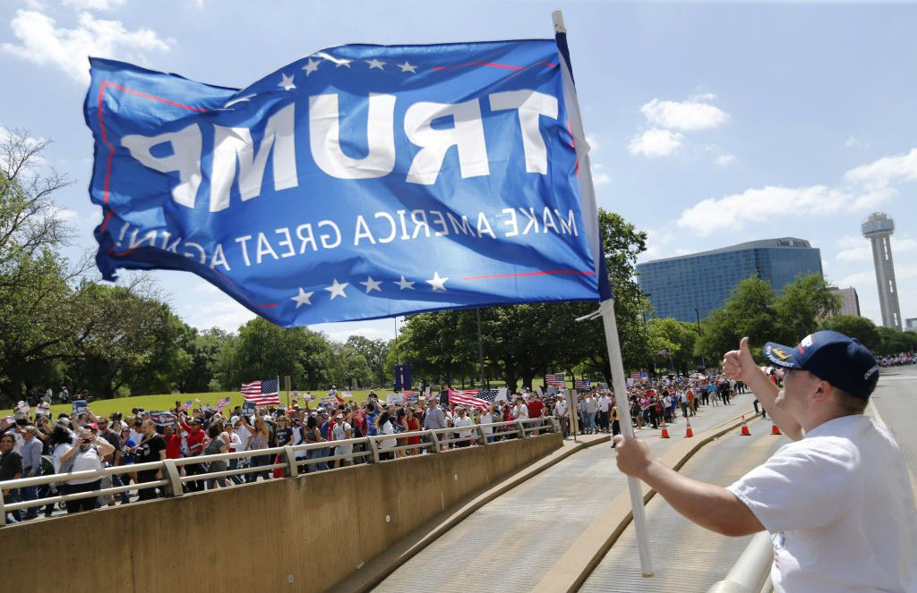Trump supporter Dustin Marvin of Dallas posts up across the street as people march towards Dallas City Hall during the Mega March in Dallas on Sunday, April 9, 2017. (Vernon Bryant/The Dallas Morning News)