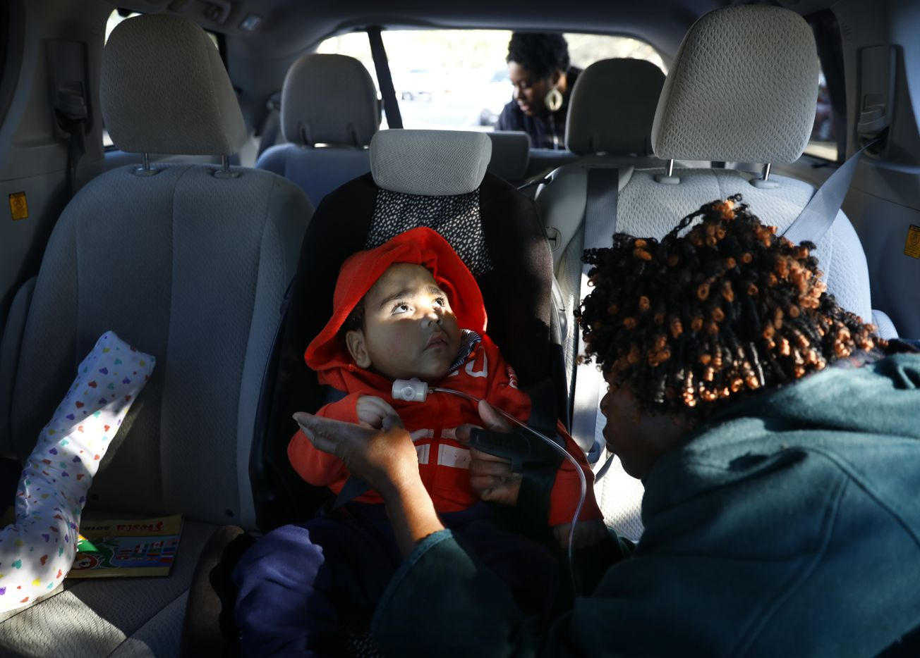 D'ashon's nurse straps him into his car seat after his checkup at a Dallas clinic.