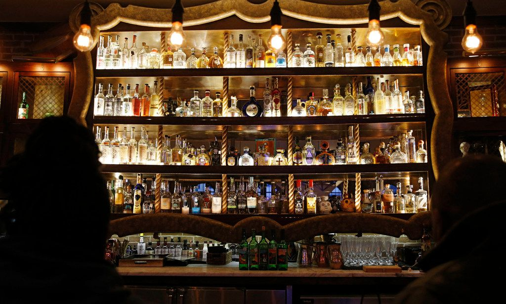 The center section of the bar at Mexican Sugar in Plano features many different types of mezcal and tequila.