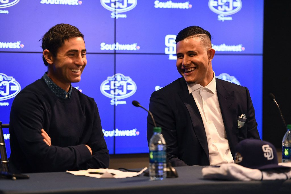 PEORIA, ARIZONA - FEBRUARY 22: Manny Machado #8 of the San Diego Padres shares a laugh alongside side Executive V.P./General Manager A.J. Preller at Peoria Stadium on February 22, 2019 in Peoria, Arizona. (Photo by Jennifer Stewart/Getty Images)