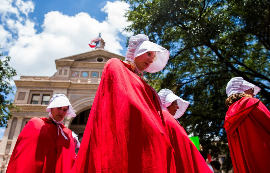 Women dressed as handmaidens walk through a One Texas Resistance rally on the south steps of the Capitol on the first day of a legislative special session on Tuesday, July 18, 2017 at the Texas state capitol in Austin.