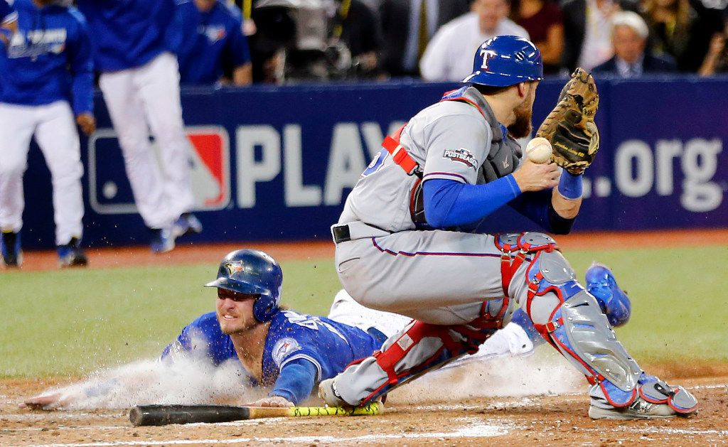 Toronto Blue Jays Josh Donaldson (20) slides into home to win the game in extra innings as Texas Rangers catcher Jonathan Lucroy (25) can't get a handle on the ball in Game 3 of the ALDS Series at Rogers Centre in Toronto, Ontario, Sunday, October 9, 2016. The Rangers were swept in the series, 3-0. (Tom Fox/The Dallas Morning News)