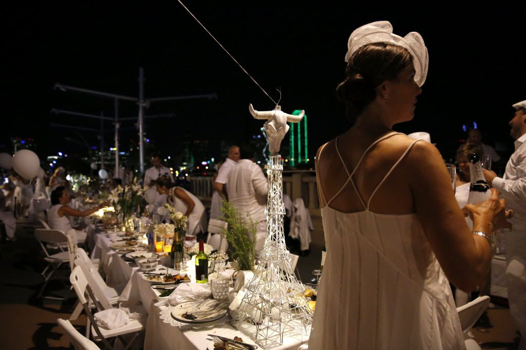 A longhorn sits atop an Eiffel Tower centerpiece during the inaugural Diner en Blanc Dallas on the Continental Avenue Bridge in Dallas on Sept. 17, 2015. Exactly 1,678 people attended the event, which requires dinner guests to dress all in white and bring their own chairs and centerpieces. As per tradition, the location was kept private leading up to the event.