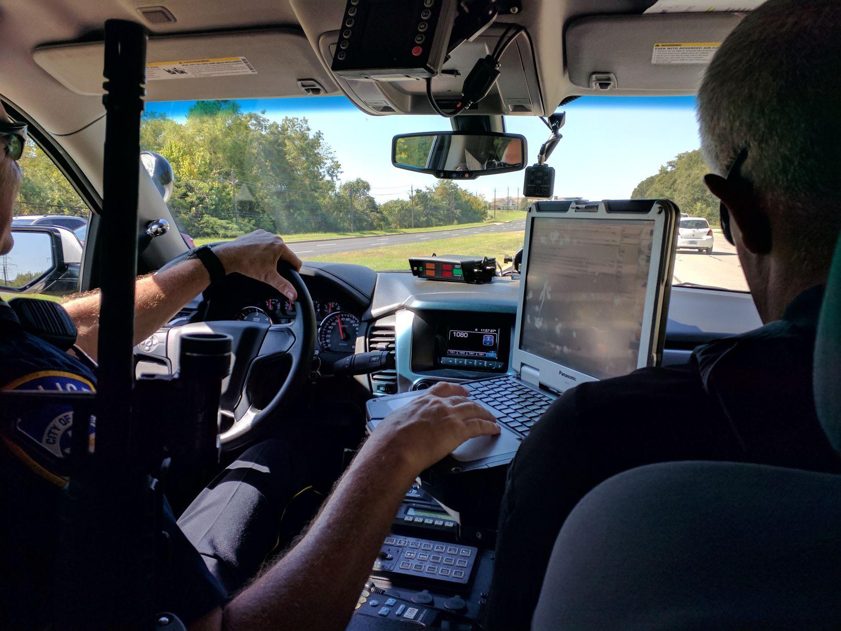 Officer Casey Sanders (left) and BIU Mental Health Coordinator Ken Bennett patrol a neighborhood in Euless in the Euless Police Department patrol car.