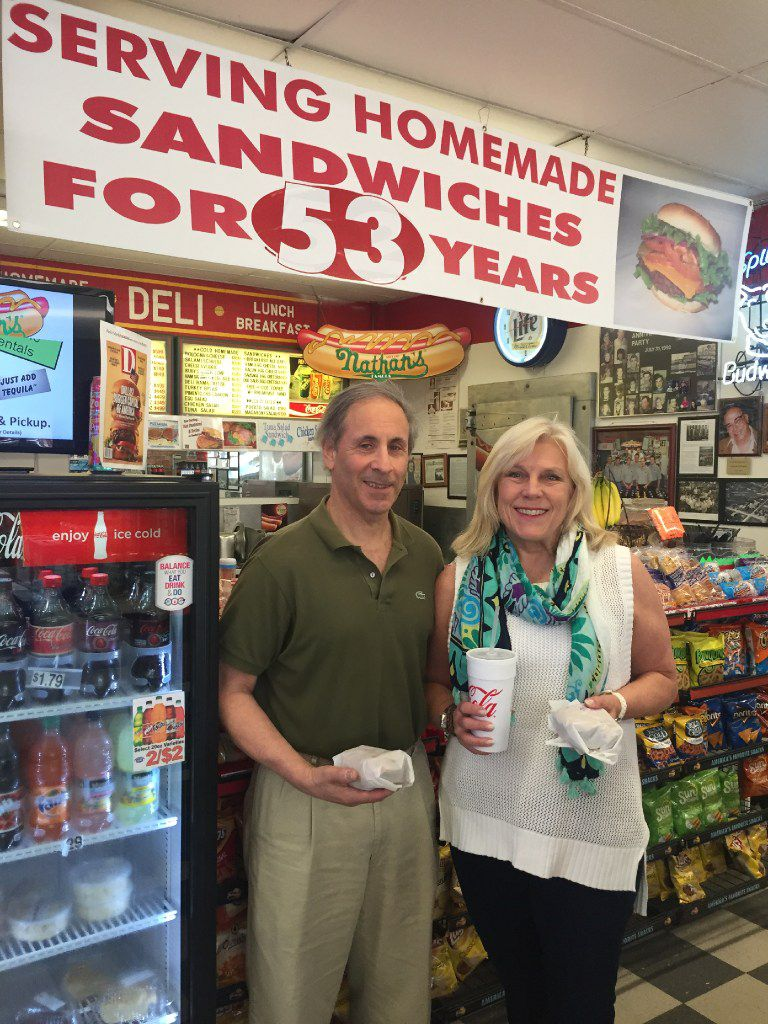 Randy and Paige Flink hold their fresh-off-the-grill burgers at Parkit Market. The Greenville Avenue convenience store and deli has been in business at the same location for more than 50 years.