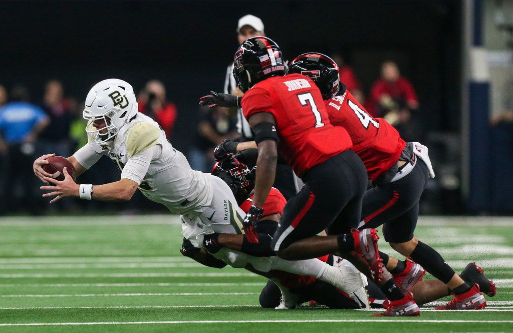 Baylor Bears quarterback Charlie Brewer (12) reaches for extra yards on a drive as he is brought down by Texas Tech Red Raiders defense during a matchup between Baylor and Texas Tech on Saturday, Nov. 24, 2018 at AT&T Stadium in Arlington, Texas. (Ryan Michalesko/The Dallas Morning News)