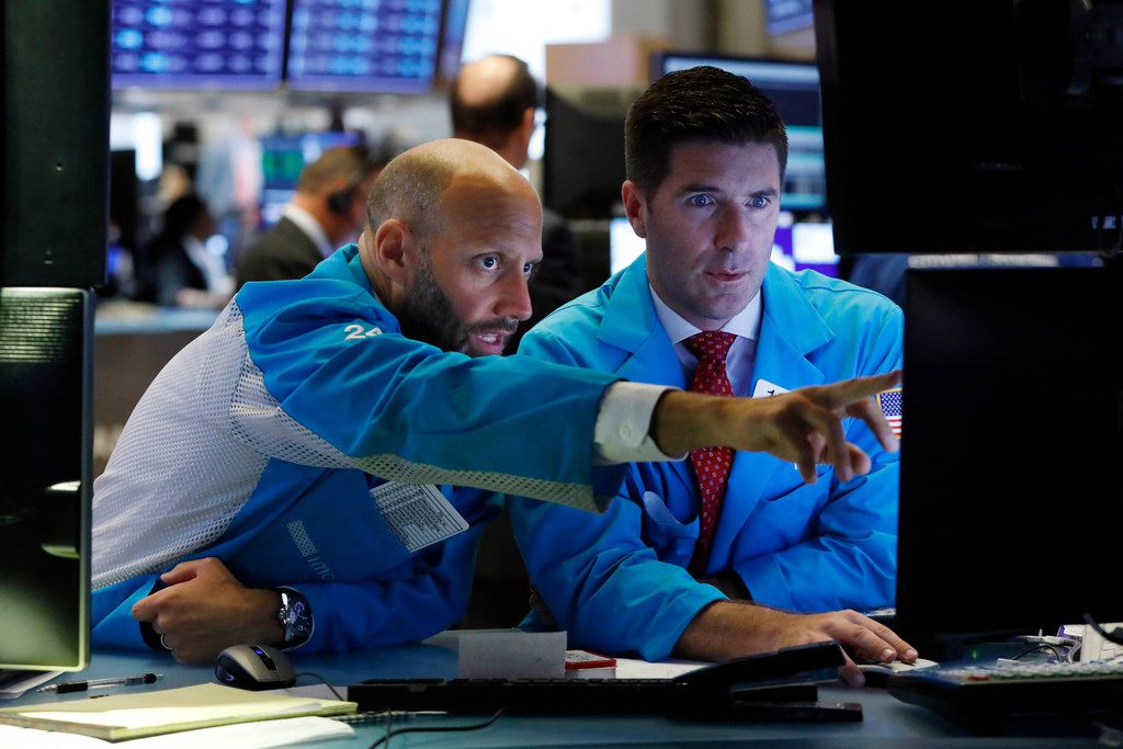 Specialists Meric Greenbaum (left) and Thomas McArdle work on the floor of the New York Stock Exchange on Aug. 6.