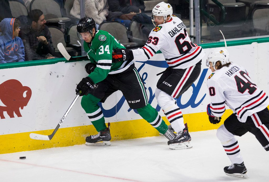 Dallas Stars right wing Denis Gurianov (34) keeps control of the puck ahead of Chicago Blackhawks defenseman Carl Dahlstrom (63) and right wing John Hayden (40) during the first period of an NHL game between the Dallas Stars and the Chicago Blackhawks on Thursday, December 20, 2018 at American Airlines Center in Dallas. (Ashley Landis/The Dallas Morning News)