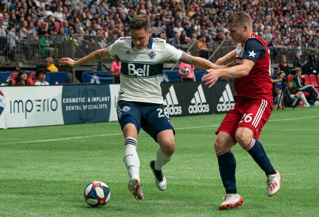 Vancouver Whitecaps' Jakob Nerwinski, left, tries to keep FC Dallas' John Nelson away from the ball during the second half of an MLS soccer match Saturday, May 25, 2019, in Vancouver, British Columbia. (Richard Lam/The Canadian Press via AP)